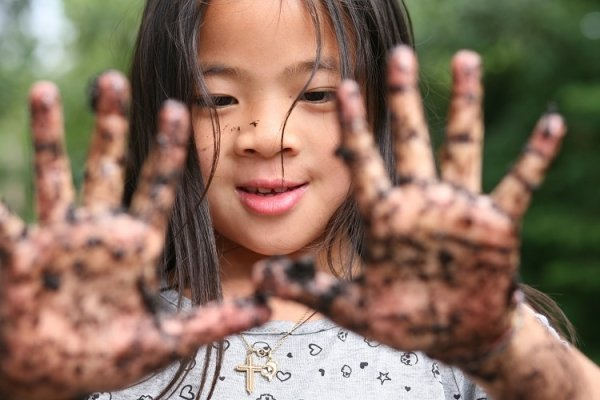 close up of child showing two dirty hands